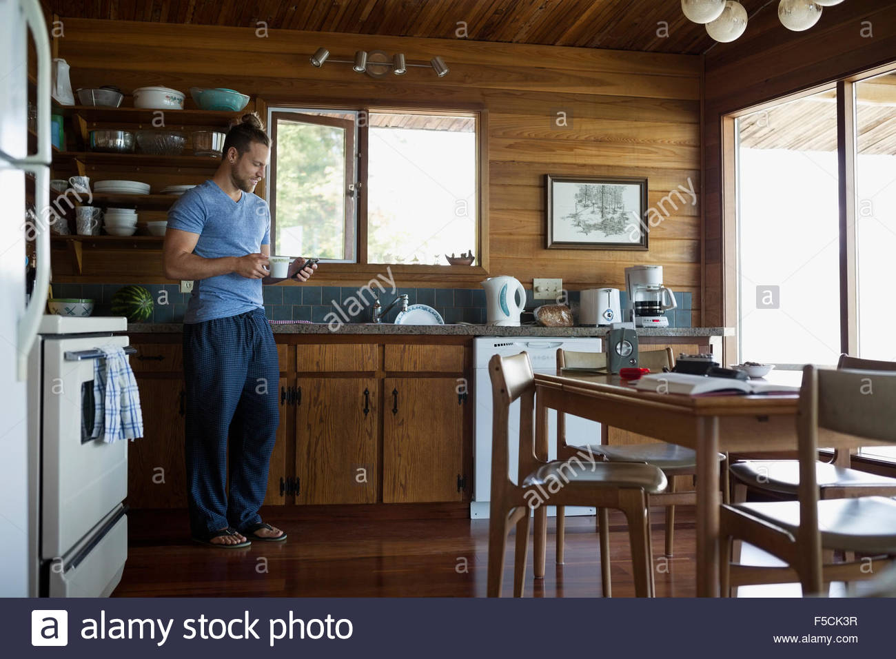 Man Drinking Coffee And Texting In Cabin Kitchen