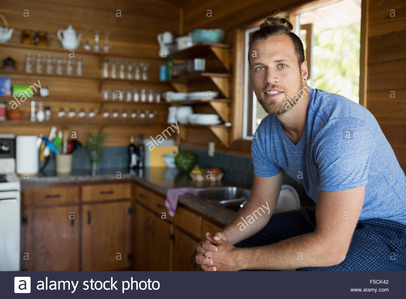 Portrait young man sitting in cabin kitchen - Stock Image
