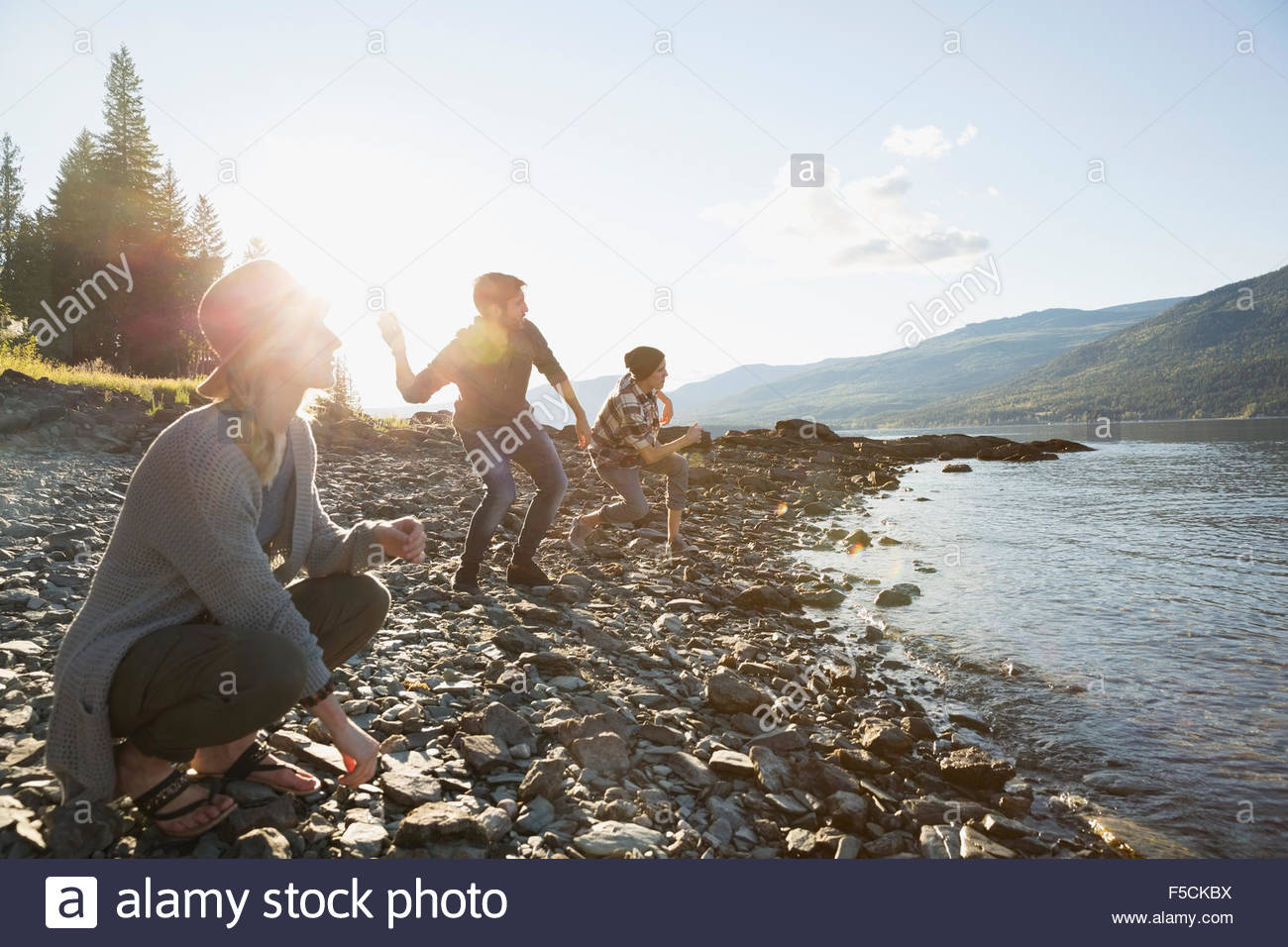 Young friends skipping stones at lakeside - Stock Image