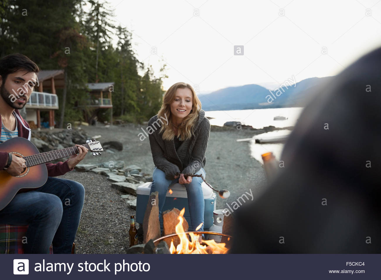 Young friends roasting marshmallows playing guitar lakeside campfire - Stock Image
