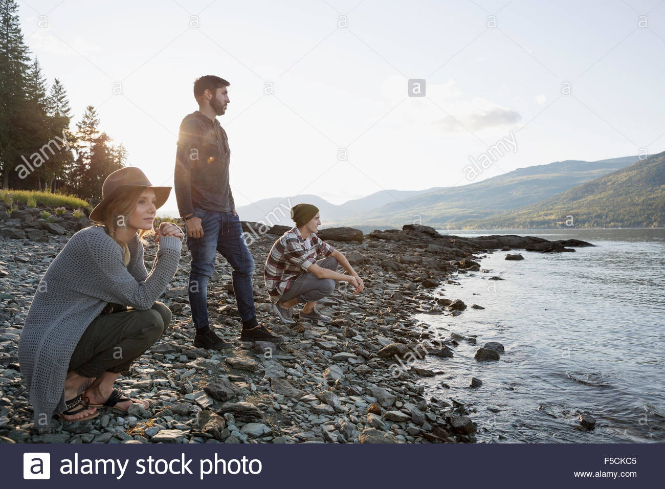 Pensive young friends at craggy lakeside - Stock Image