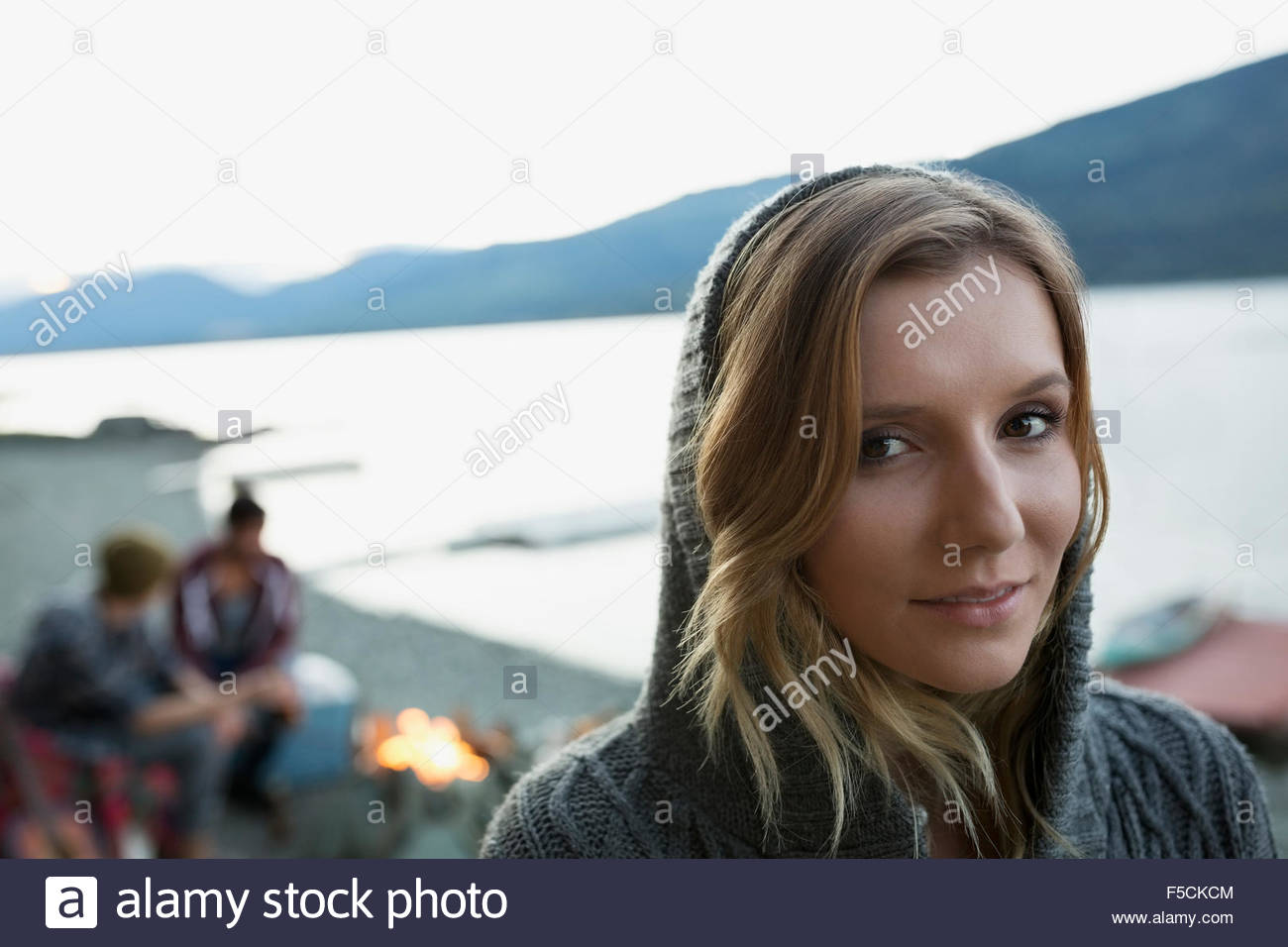 Close up portrait young woman in hoody lakeside - Stock Image
