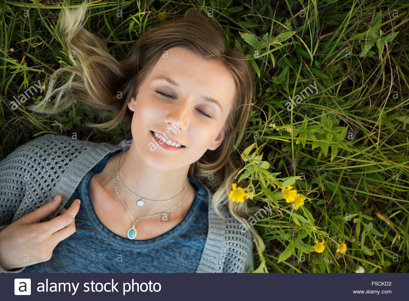 Overhead view serene young woman laying in grass - Stock Image
