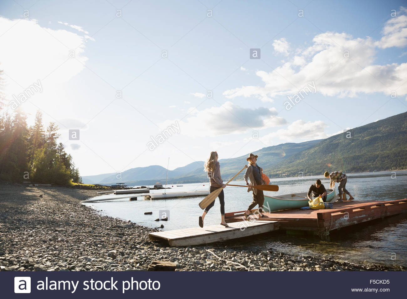 Young friends canoe and paddles on lake dock - Stock Image