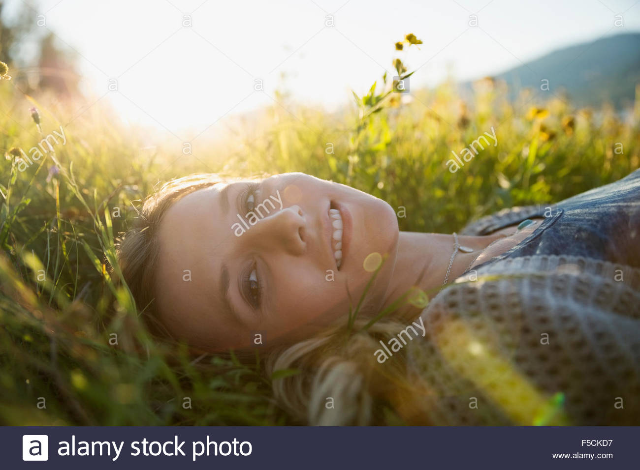 Portrait smiling young woman laying in sunny grass - Stock Image