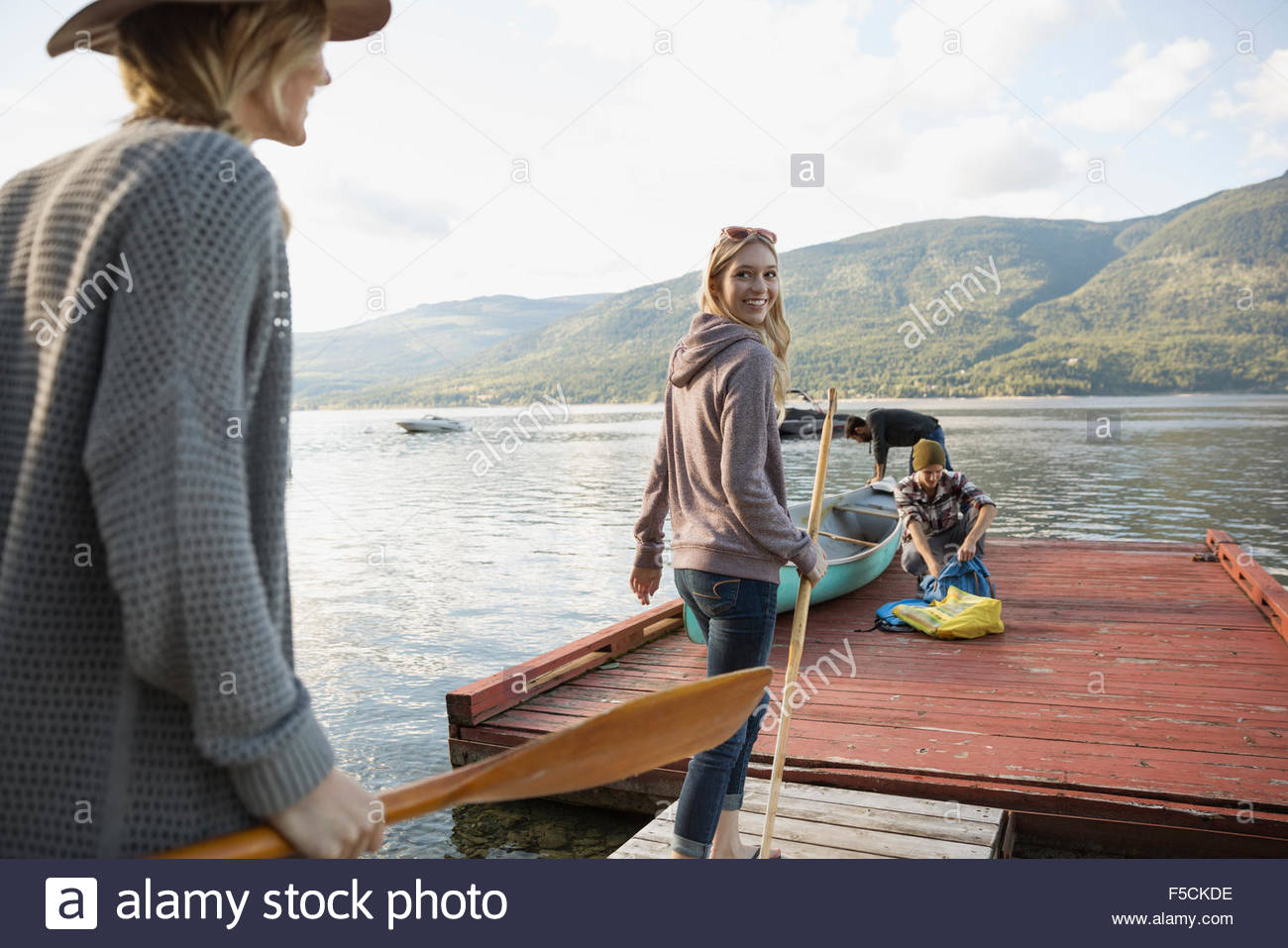Young women carrying canoe paddles on lake dock - Stock Image