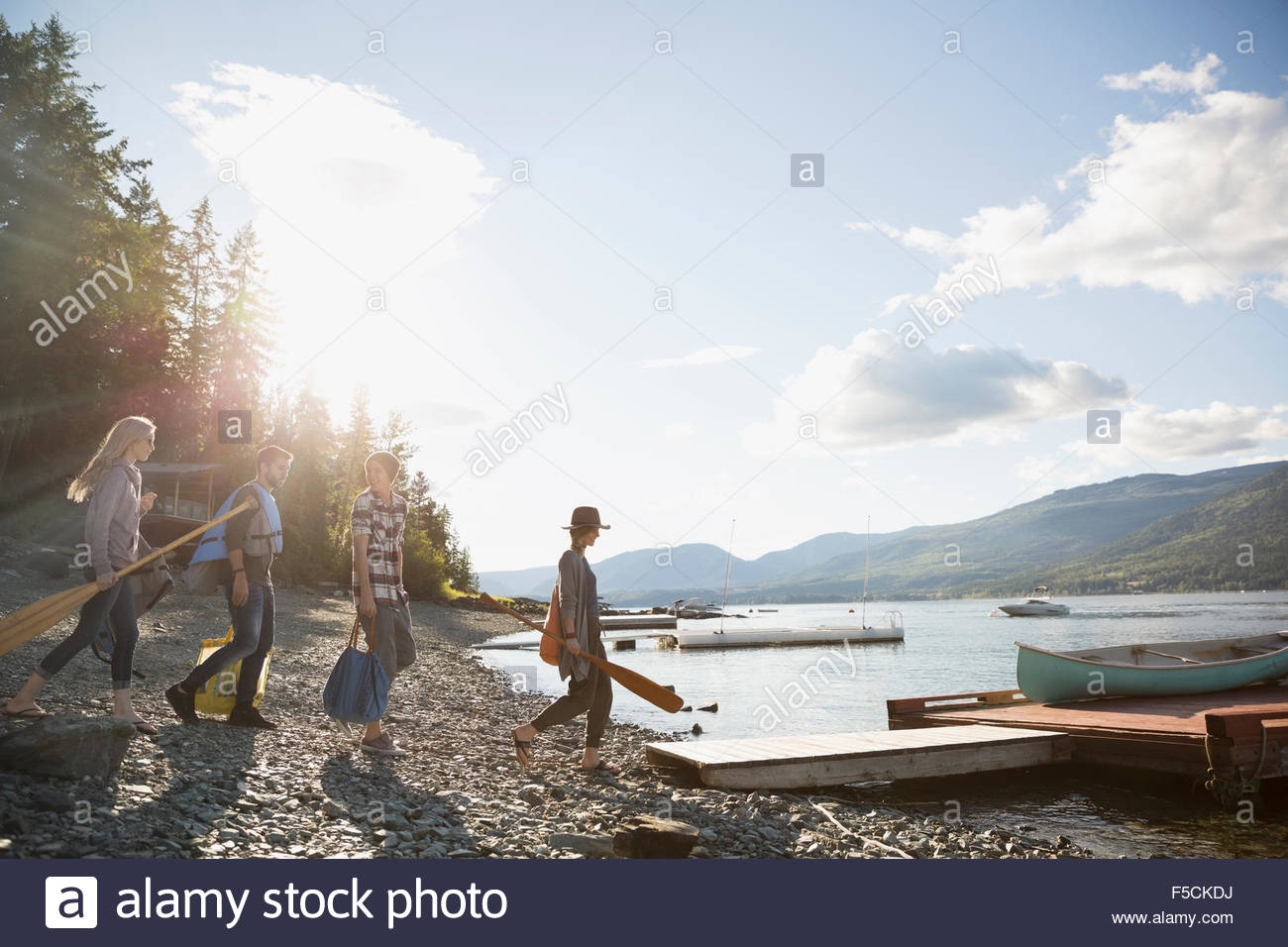 Young friends carrying canoe paddles toward lake dock - Stock Image