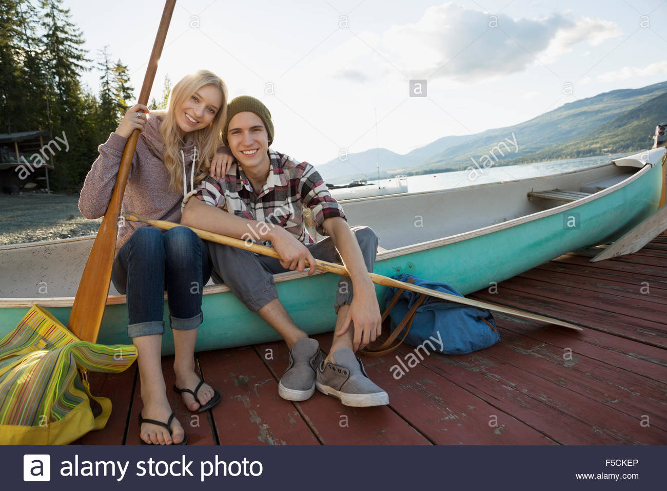 Portrait young couple with canoe and paddles dock - Stock Image