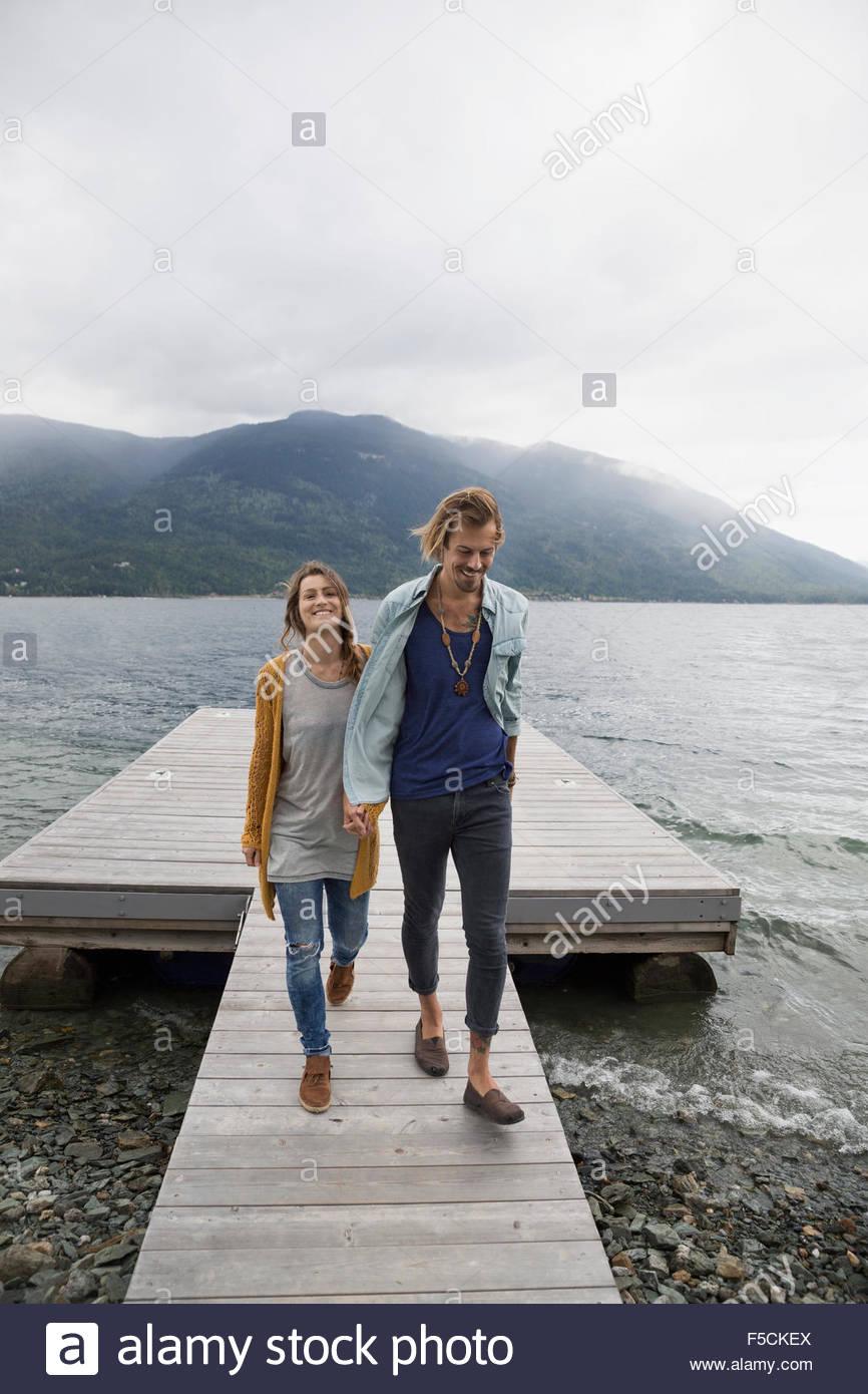 Couple walking on lake dock - Stock Image