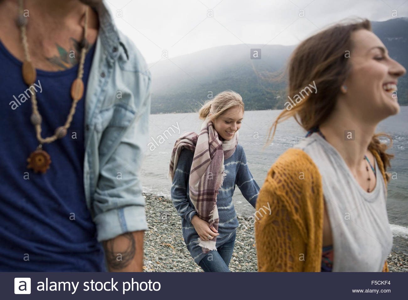 Young friends walking at lakeside - Stock Image