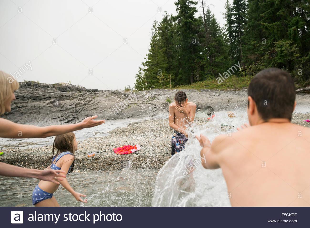 Playful family splashing son in lake - Stock Image