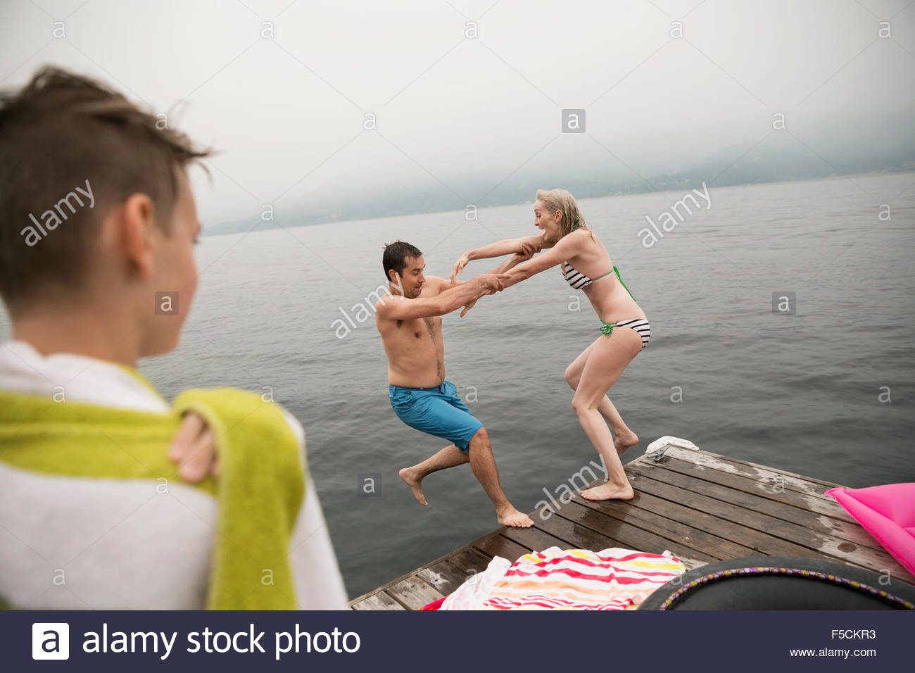 Playful woman pushing man off lake dock - Stock Image