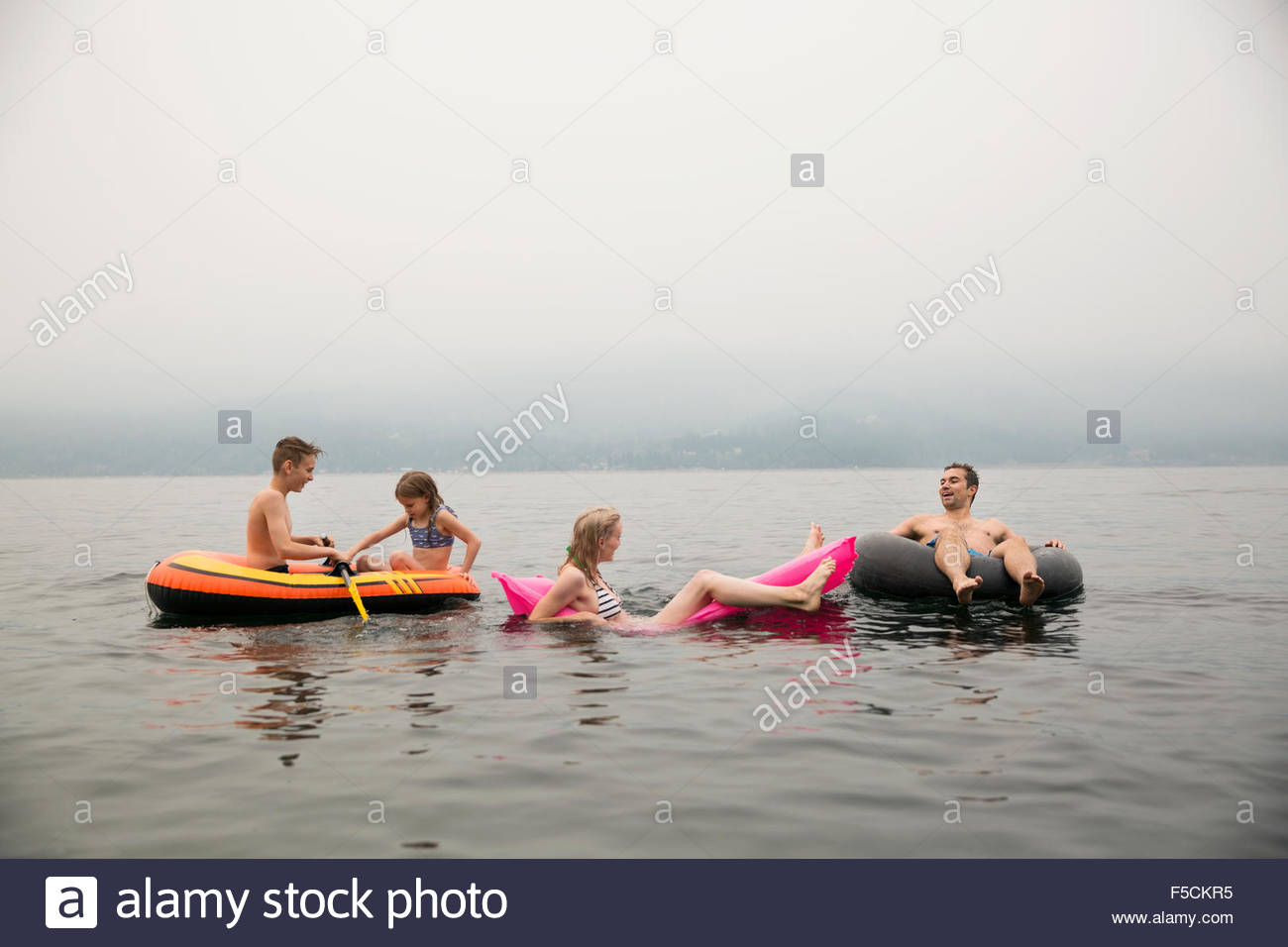 Family relaxing in pool rafts in lake - Stock Image
