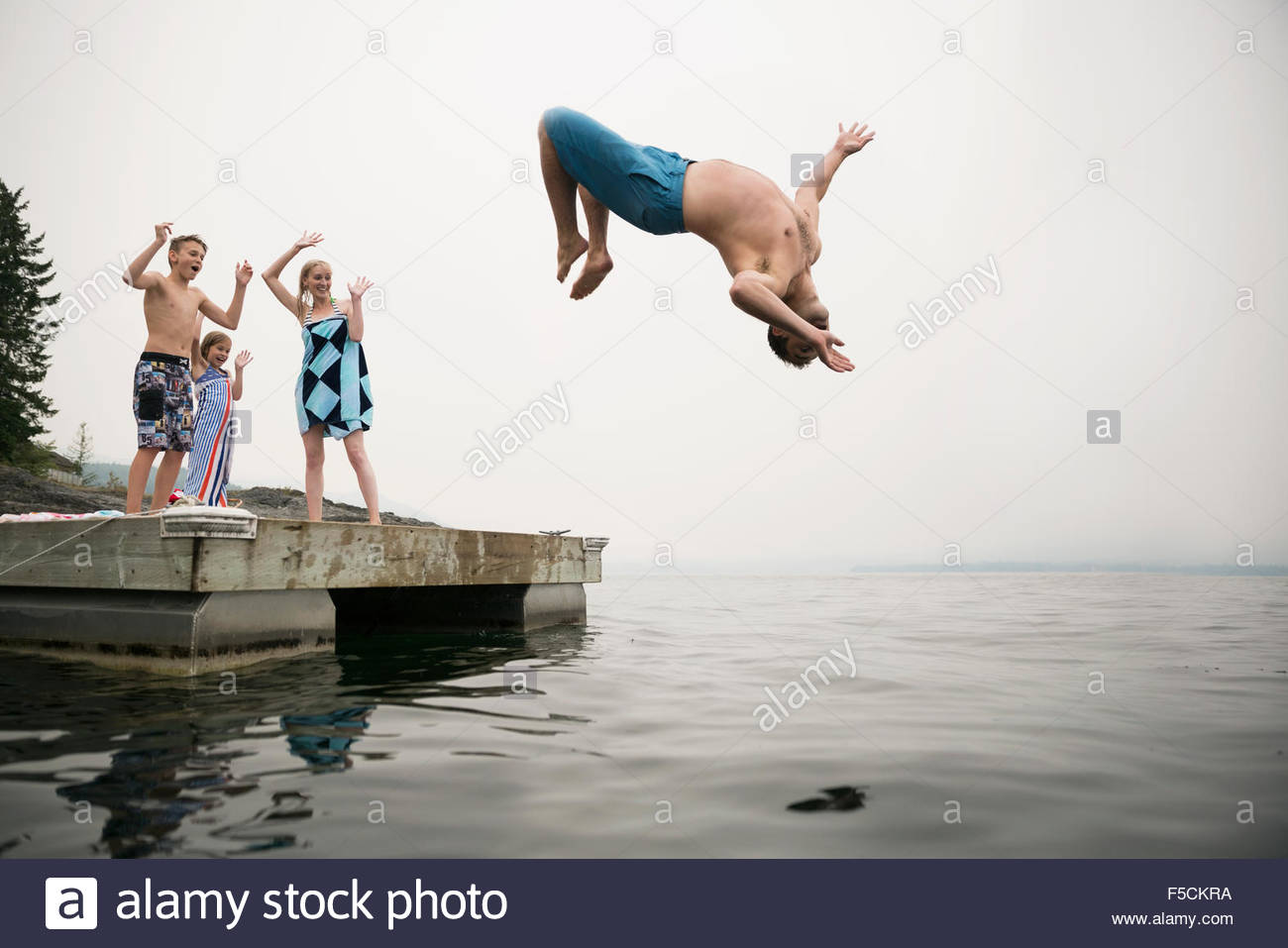 Family cheering father doing backflip into lake - Stock Image