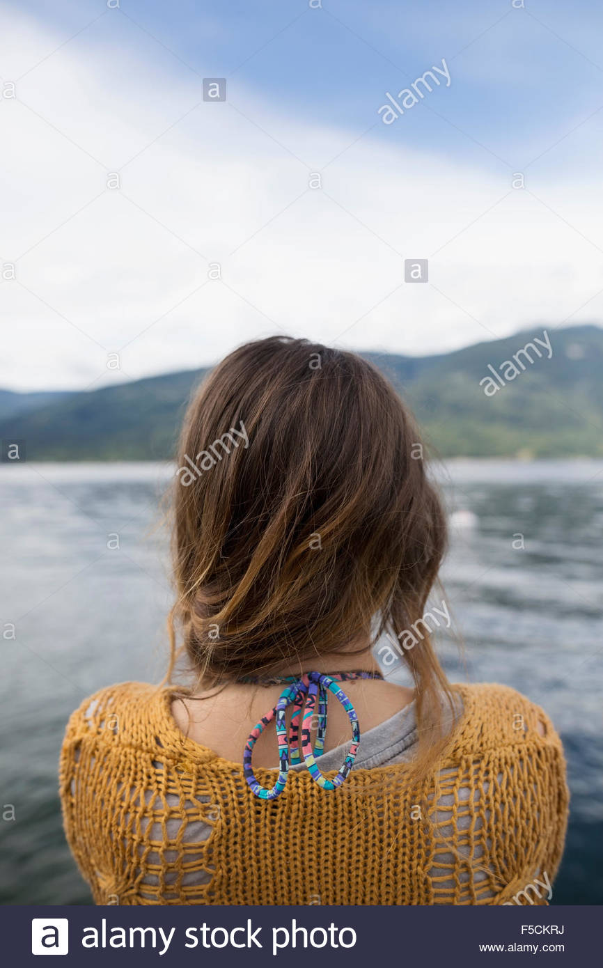 Rear view young woman looking at lake Stock Photo