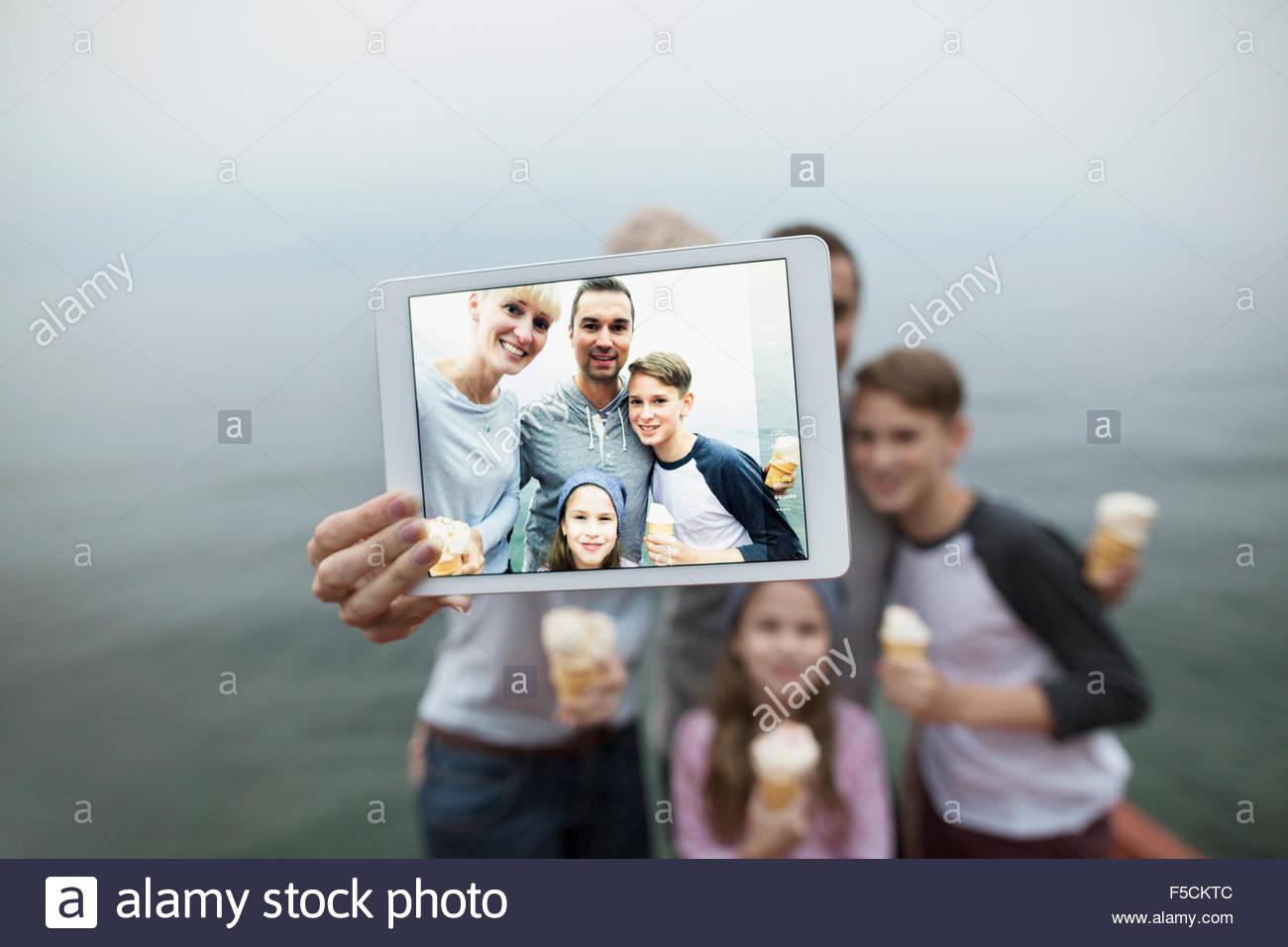 Family eating ice cream taking selfie lakeside Stock Photo
