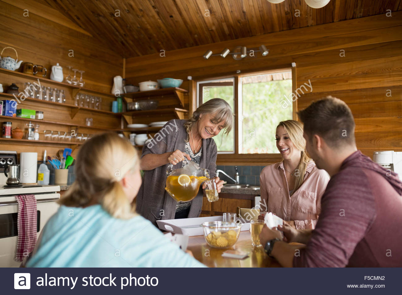 Woman pouring iced tea family cabin dining table - Stock Image
