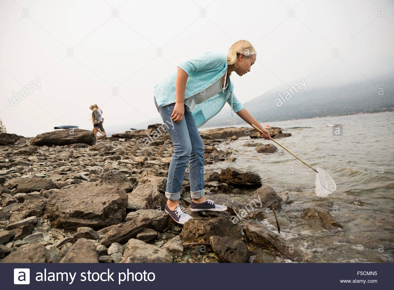 Girl fishing with net at craggy lakeside - Stock Image