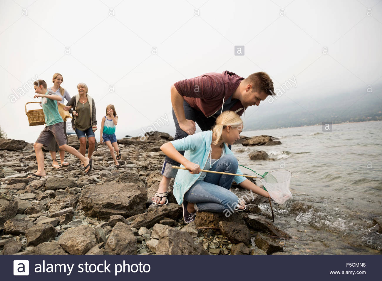 Father and daughter fishing with net craggy lakeside - Stock Image