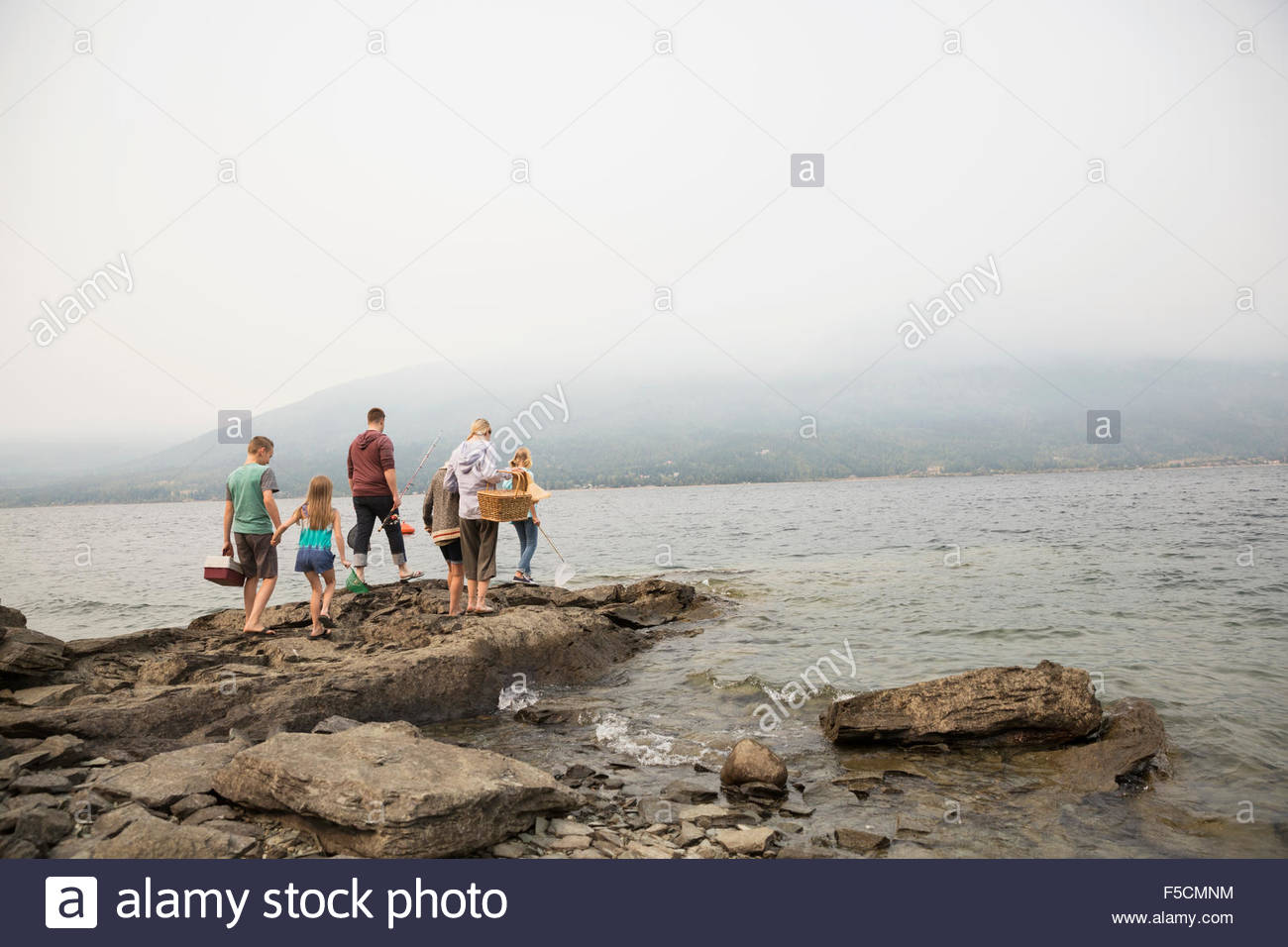 Family with fishing rods tackle box rocks lakeside - Stock Image
