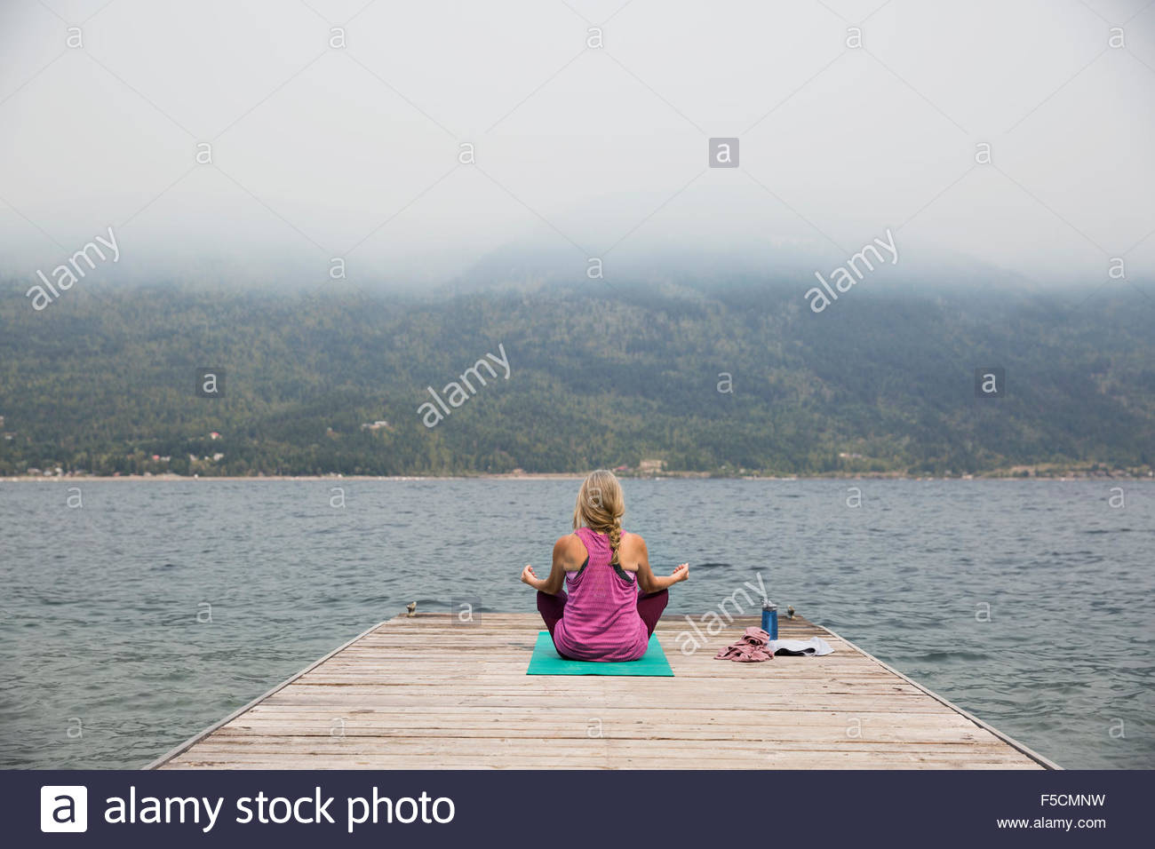 Mature woman lotus position yoga mat overlooking lake - Stock Image