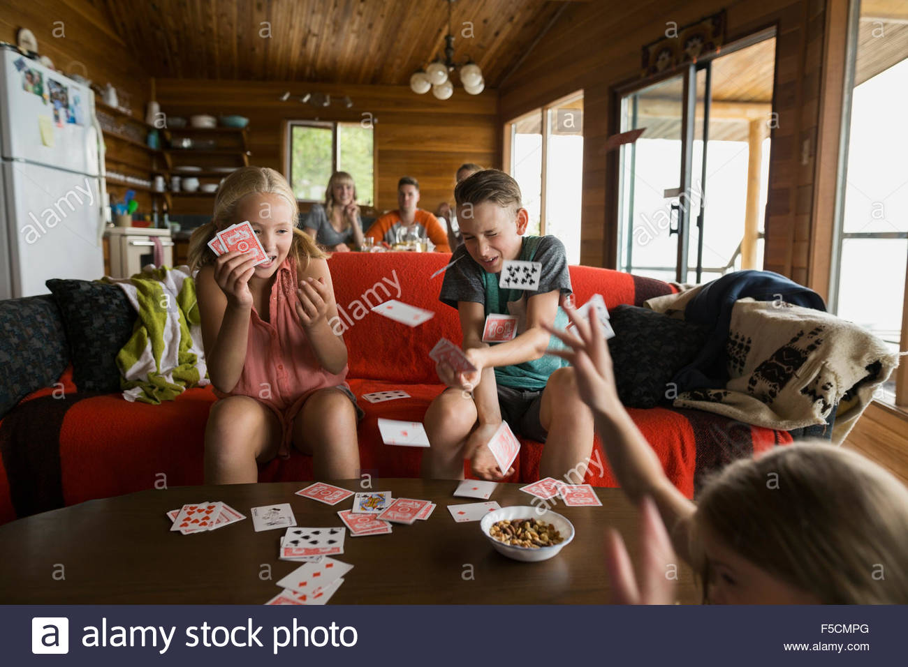 Playful cousins flicking cards in cabin Stock Photo