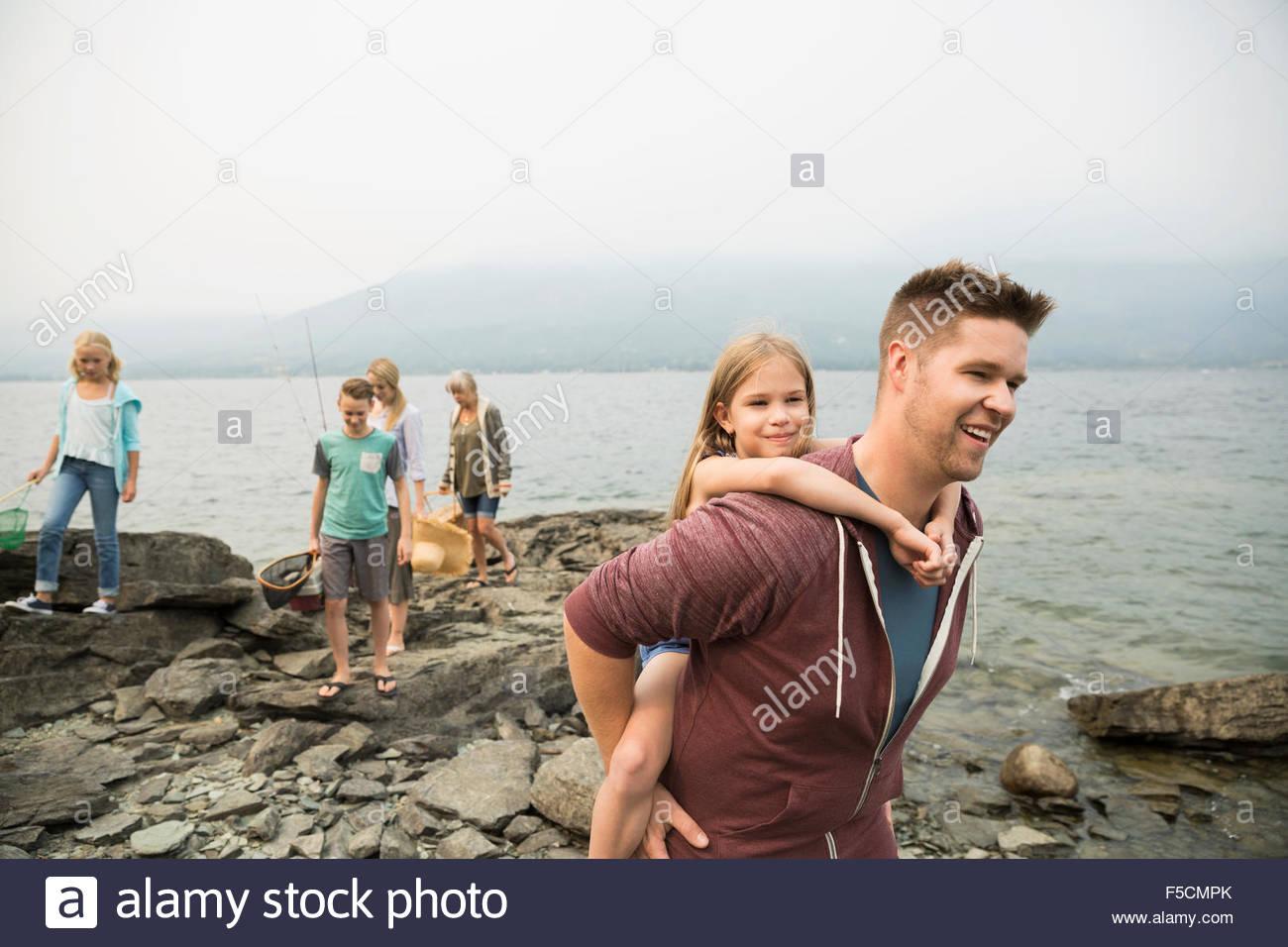 Father piggybacking daughter at craggy lakeside - Stock Image
