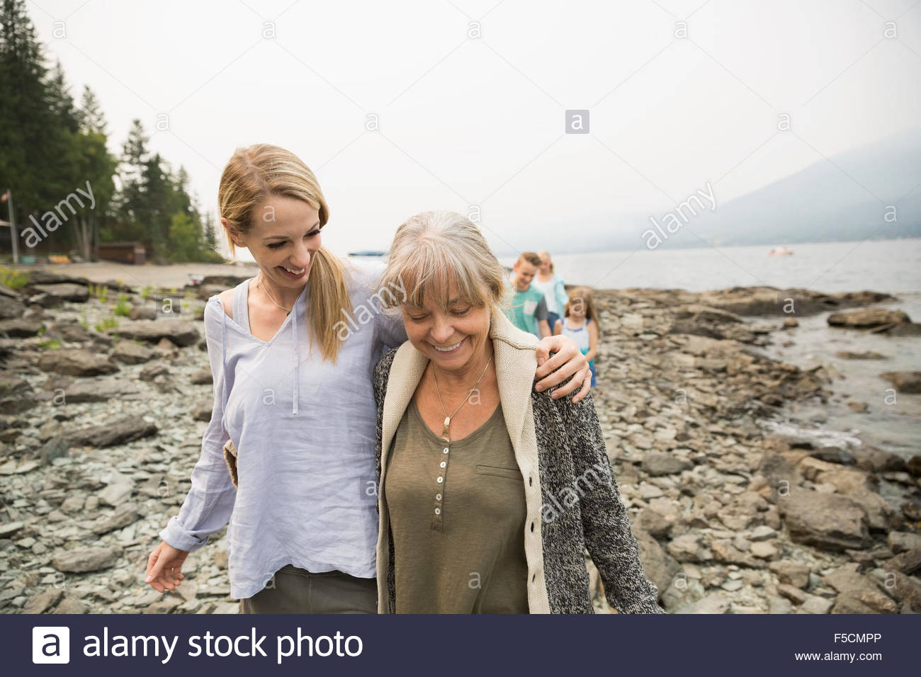 Mother and daughter walking along craggy lakeside - Stock Image