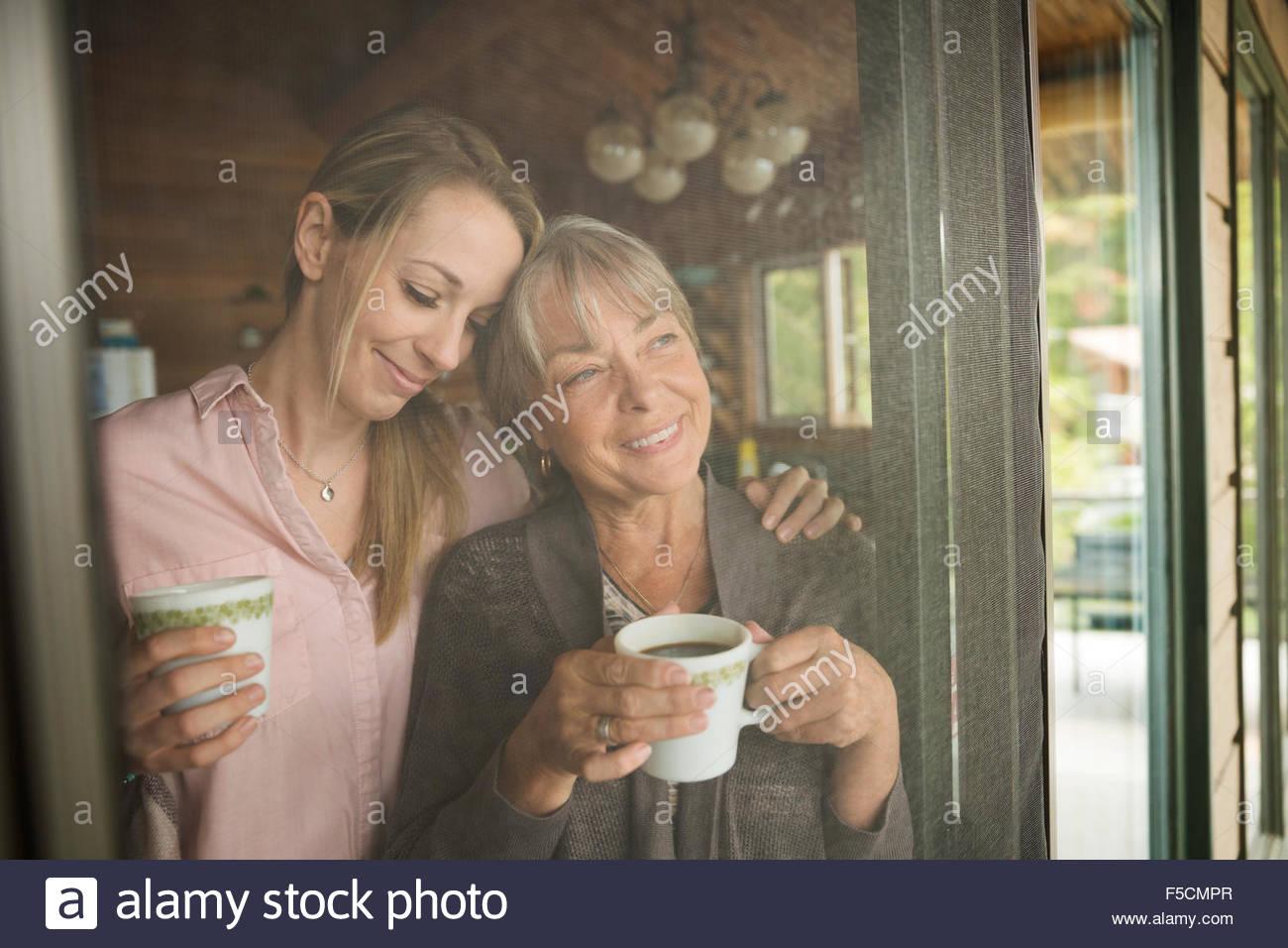 Smiling mother daughter drinking coffee cabin screen door - Stock Image