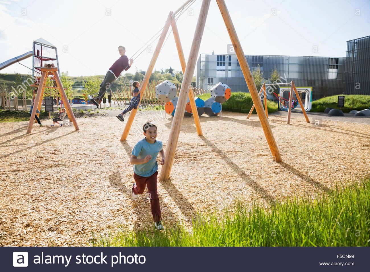 Boy running at sunny playground - Stock Image