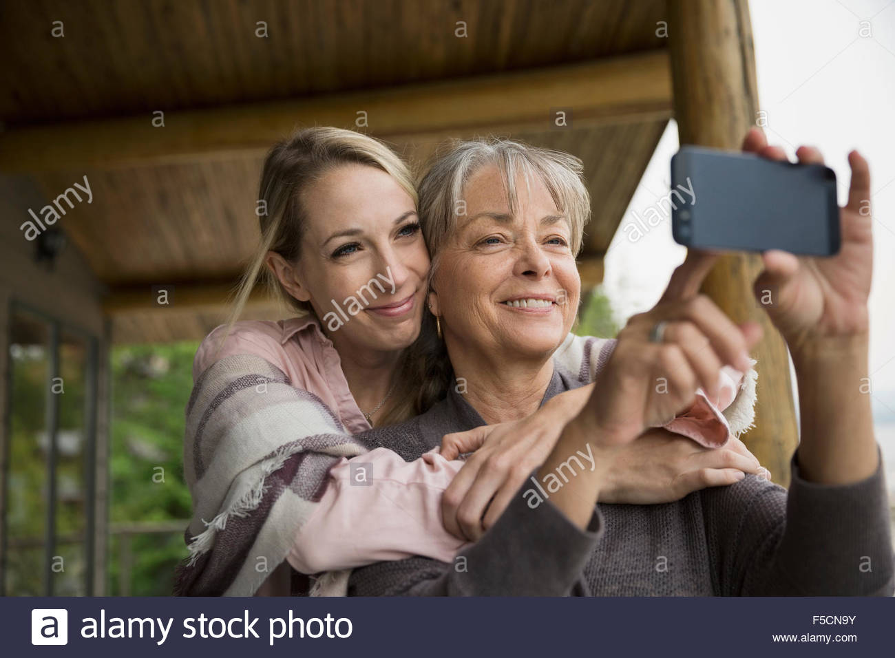Mother and daughter hugging taking selfie - Stock Image