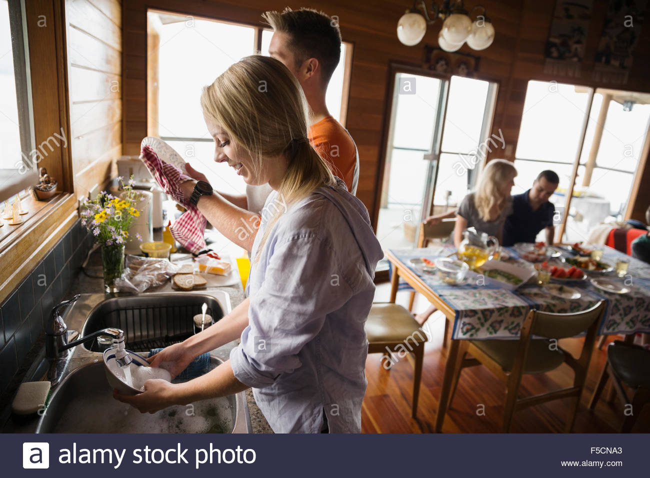 Couple washing dishes in cabin kitchen - Stock Image