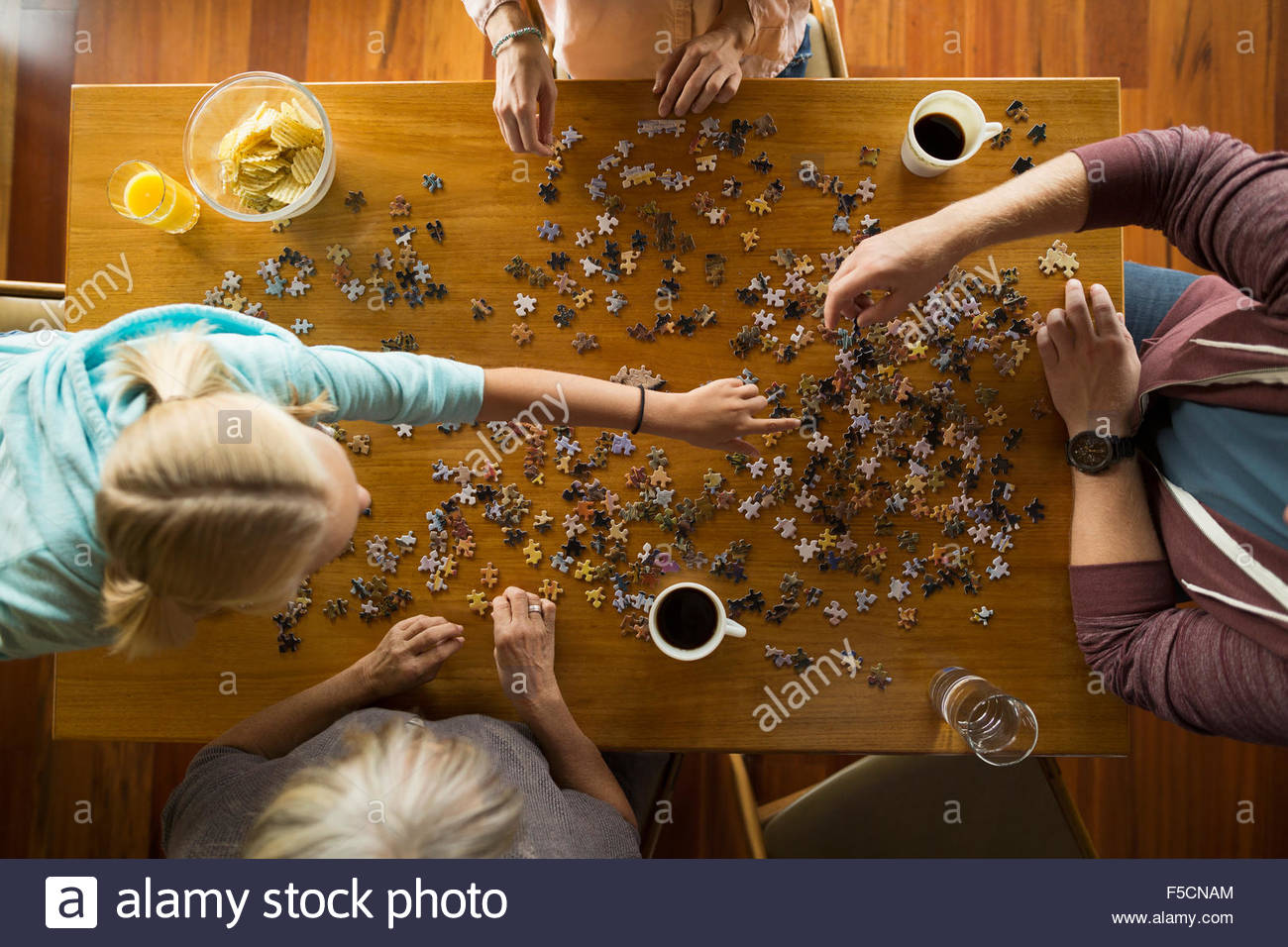 Overhead view family assembling jigsaw puzzle at table - Stock Image