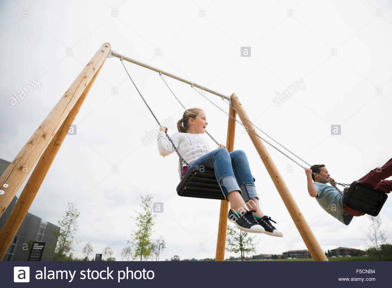 Boy and girl swinging at playground - Stock Image