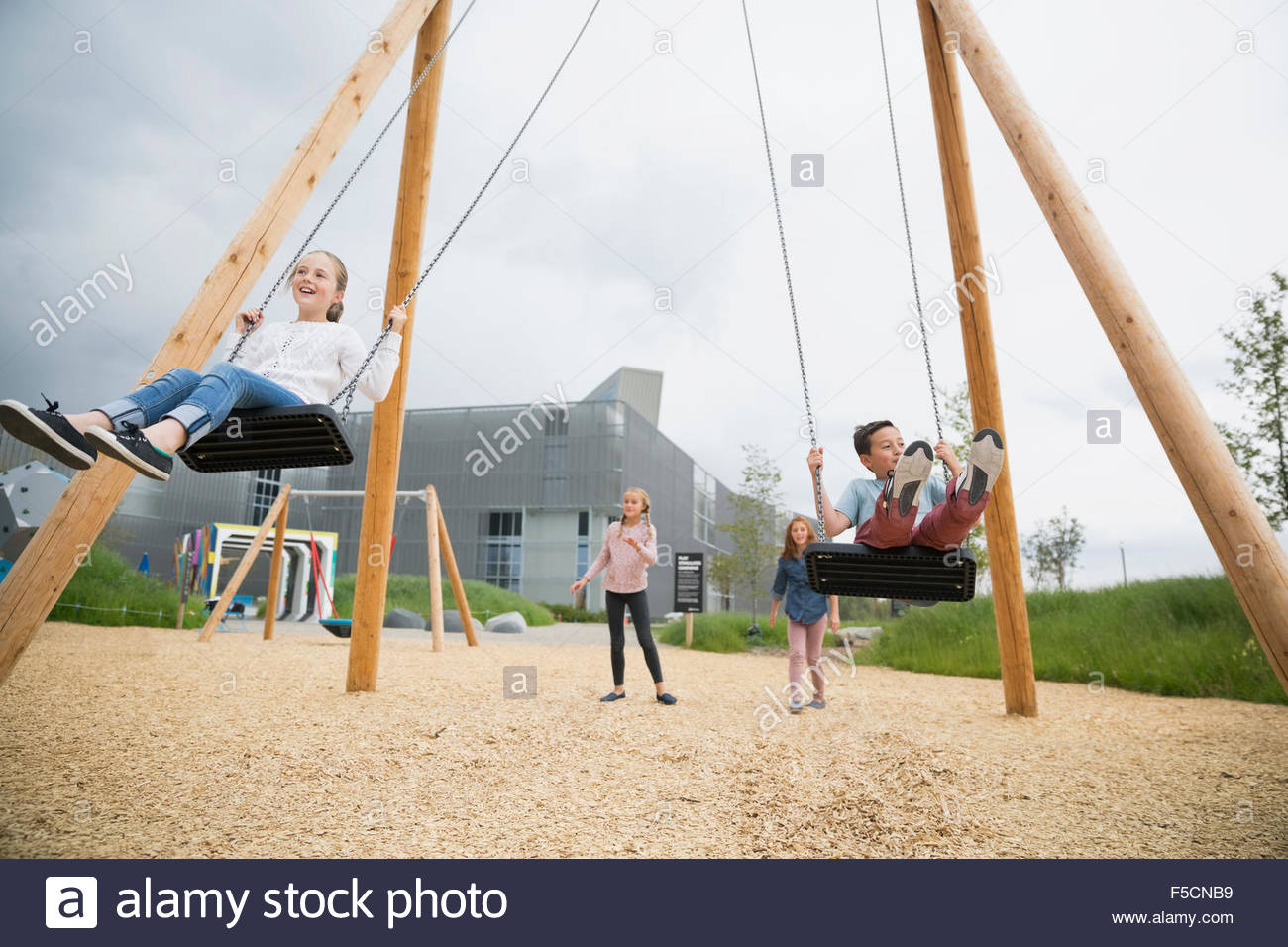 Girls swinging at playground Stock Photo