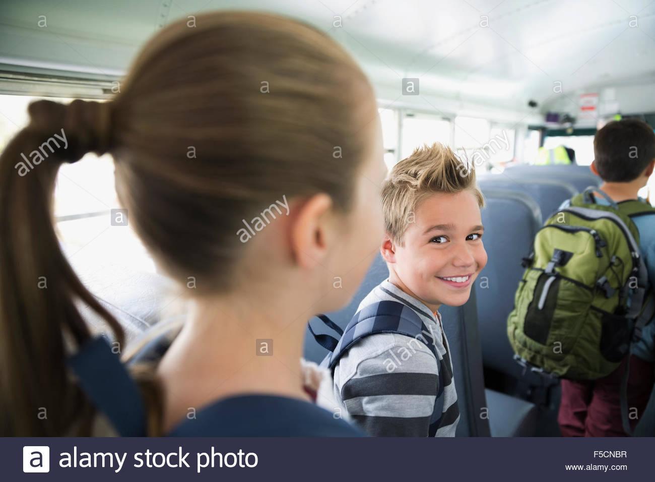 Portrait smiling schoolboy in aisle of school bus - Stock Image