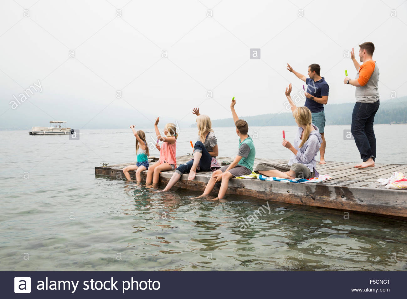 Family on dock waving to boat on lake - Stock Image