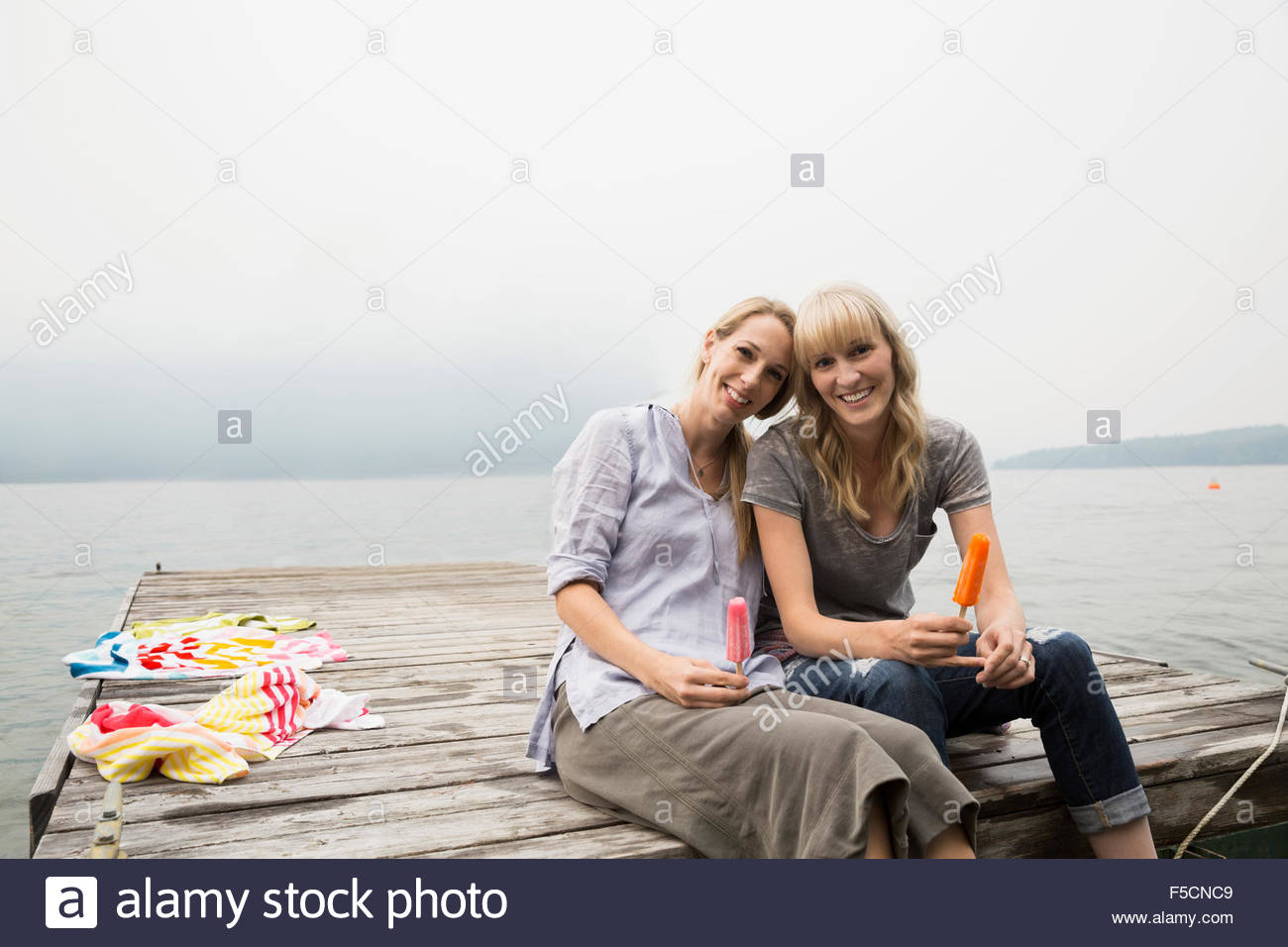 Portrait mother daughter eating flavored ice lake dock - Stock Image