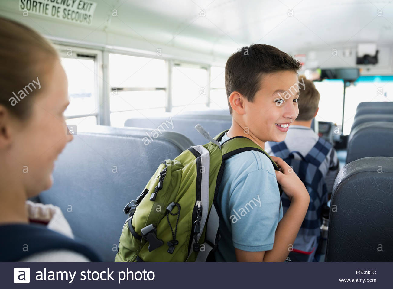 Smiling schoolboy with backpack in aisle school bus - Stock Image
