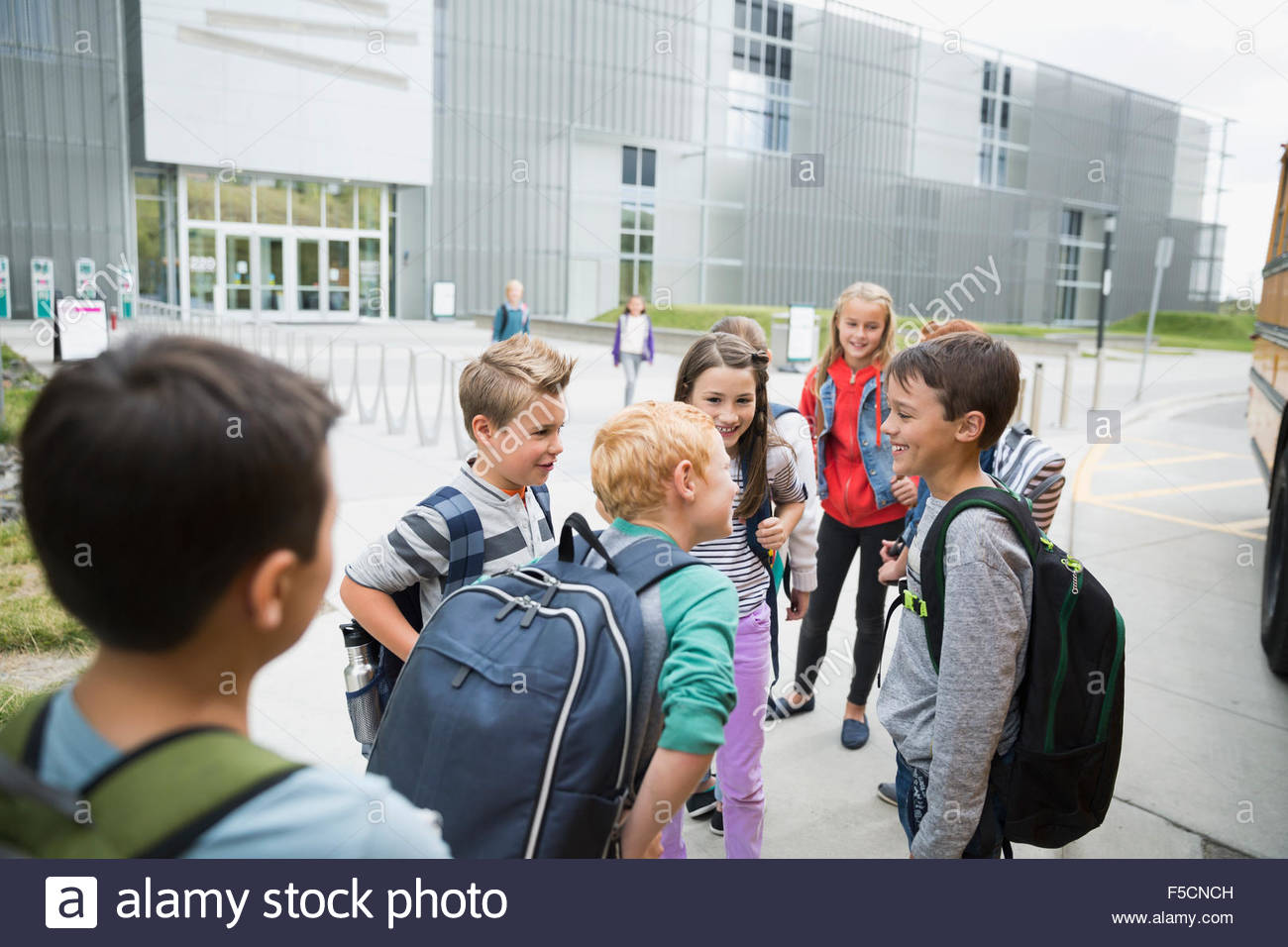 School kids with backpacks talking outside science center - Stock Image
