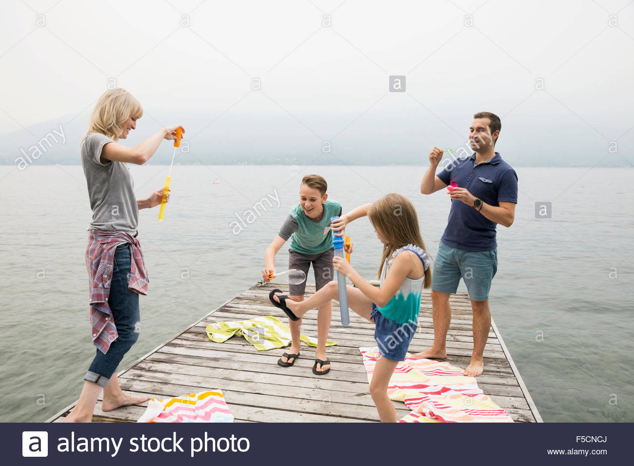 Family playing with bubbles on lake dock Stock Photo