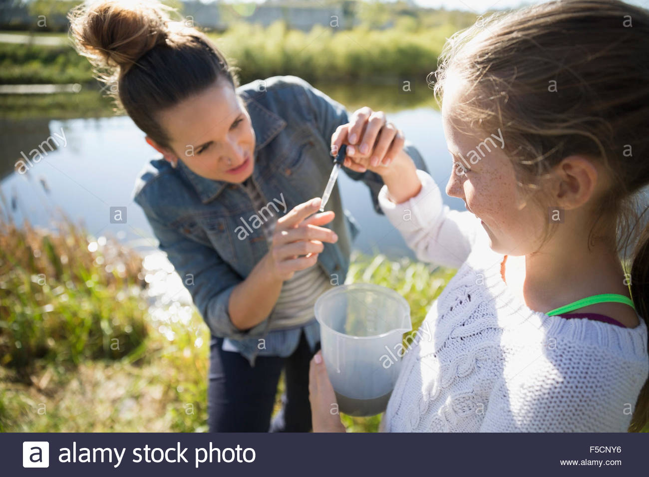 Science teacher and student testing water field trip - Stock Image