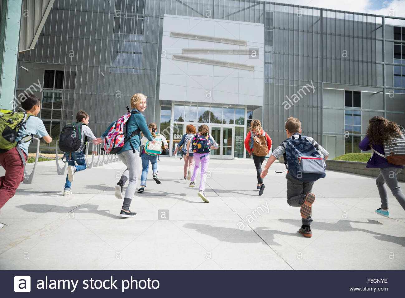 Enthusiastic school kids running toward science center entrance - Stock Image