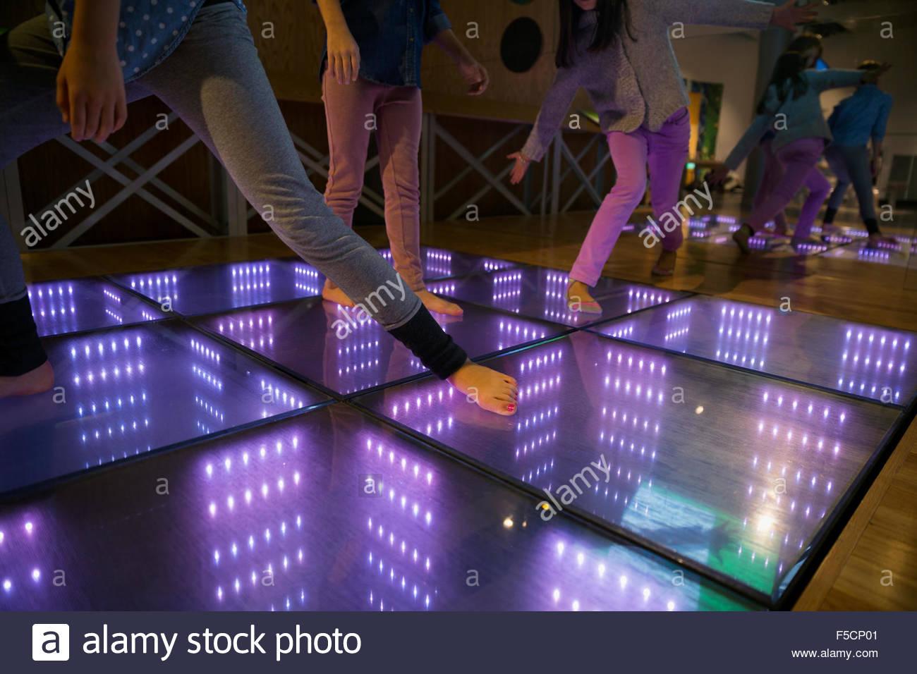 Barefoot girls dancing illuminated floor science center exhibit - Stock Image