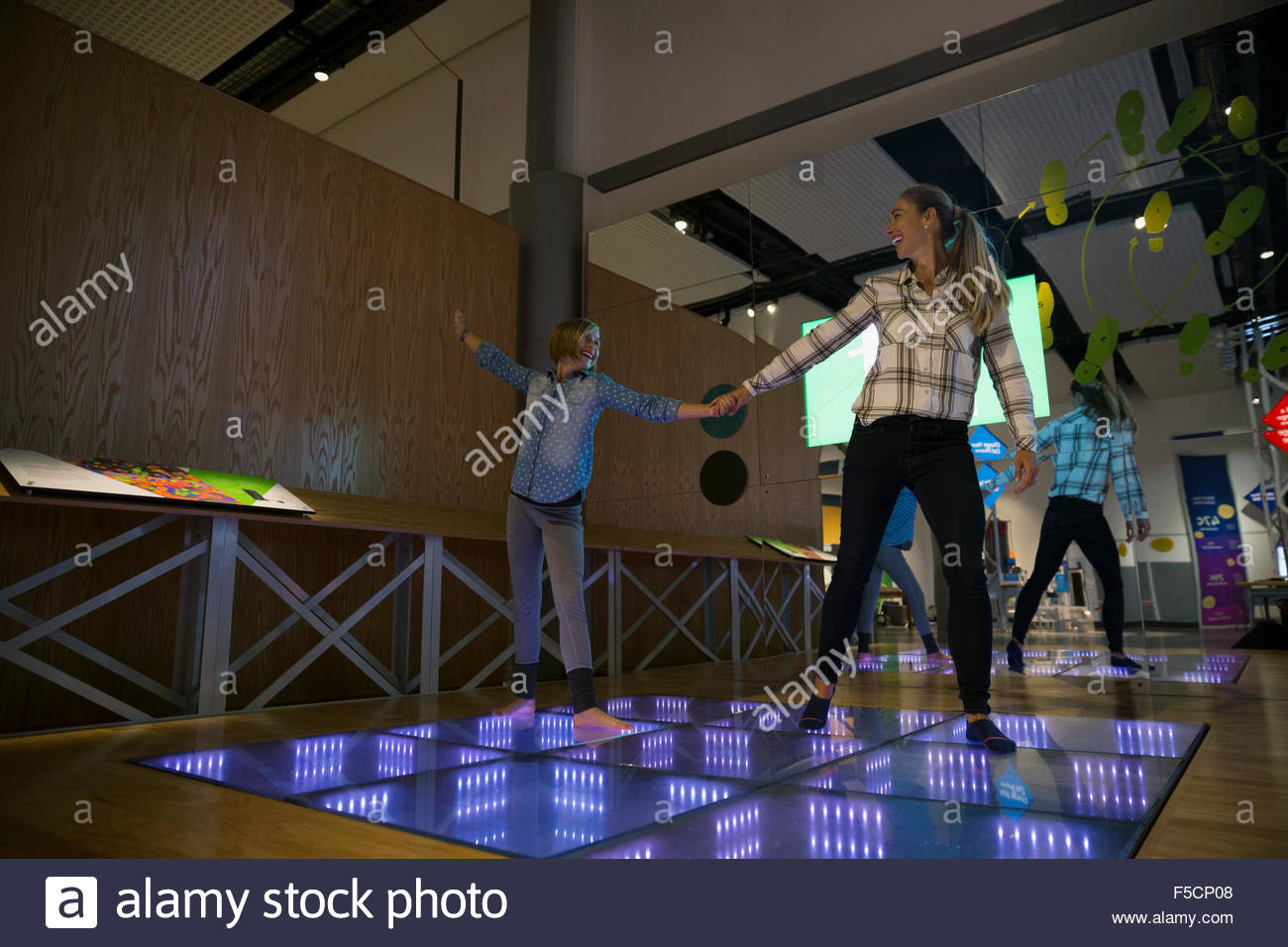 Mother daughter dancing illuminated floor science center exhibit - Stock Image