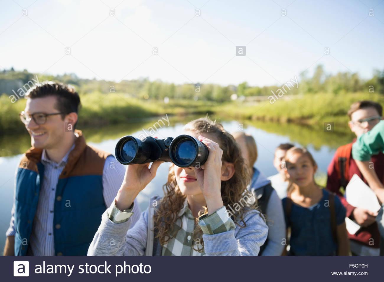 Curious schoolgirl with binoculars on field trip - Stock Image