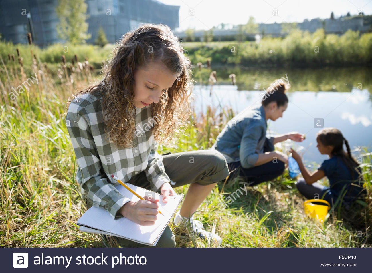 Schoolgirl taking notes on field trip at pond - Stock Image