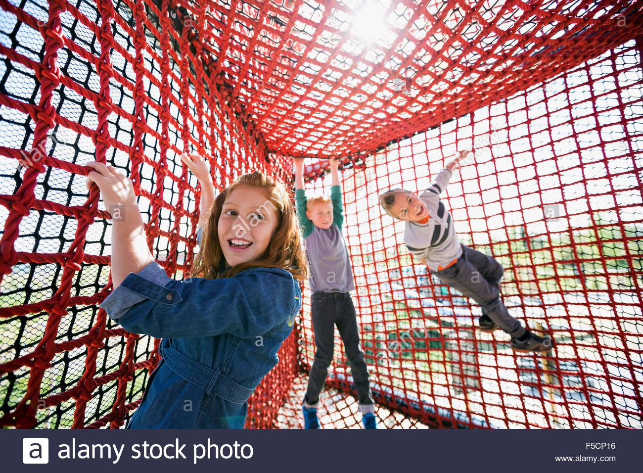Kids playing and climbing rope net sunny playground - Stock Image