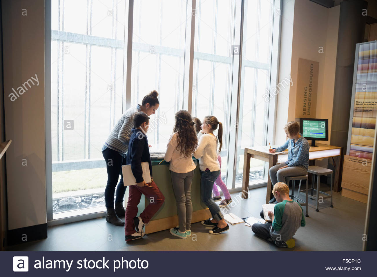 Teacher and students at exhibit in science center - Stock Image