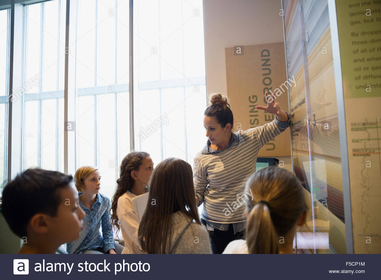 Teacher explaining exhibit to students in science center - Stock Image